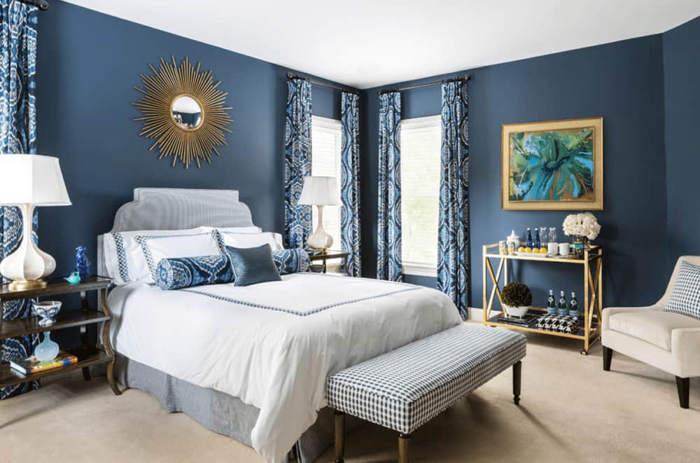 A colorful artwork and sputnik mirror add a nice accent in this blue bedroom showcasing stylish white table lamps and gray skirted bed with a patterned bench on its end.