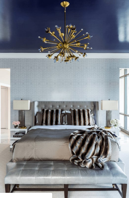 A brass sputnik chandelier hangs over the tufted wingback bed accompanied by a gray cushioned bench and white nightstands that are topped with sleek table lamps.