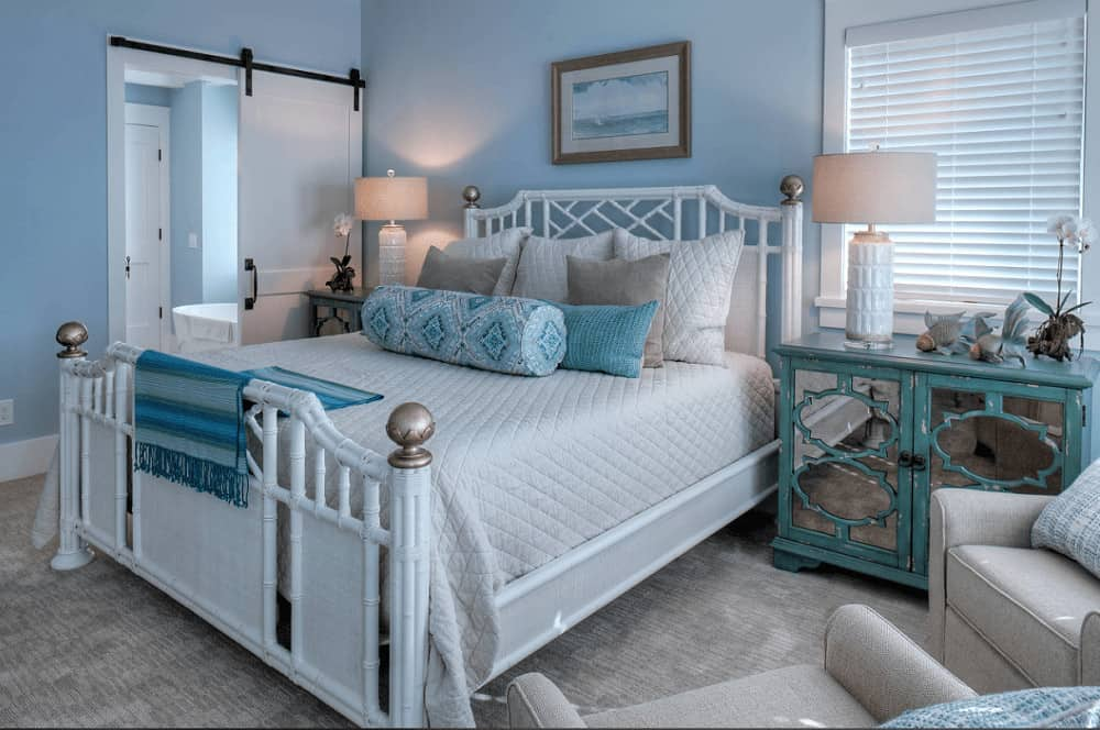 Beach style bedroom with white wicker bed and mirrored nightstands in distressed blue. It includes drum table lamps and gray armchairs that blend in with the carpet flooring.