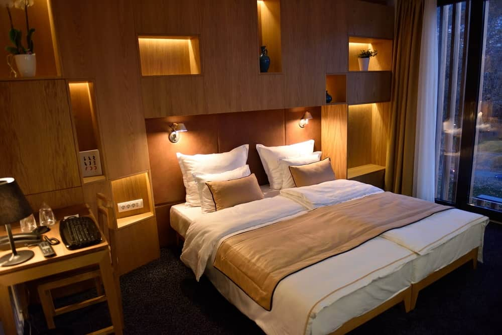 Warm primary bedroom filled with built-in shelving and bed illuminated by wall sconces. It includes wooden chair and desk topped by a black table lamp.