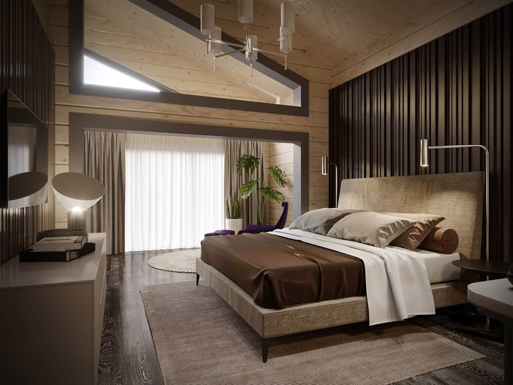 A purple lounge chair sits next to the upholstered bed lighted by chrome floor lamps and a white modern chandelier. It faces the cabinet and flat screen TV mounted on the beadboard wall.