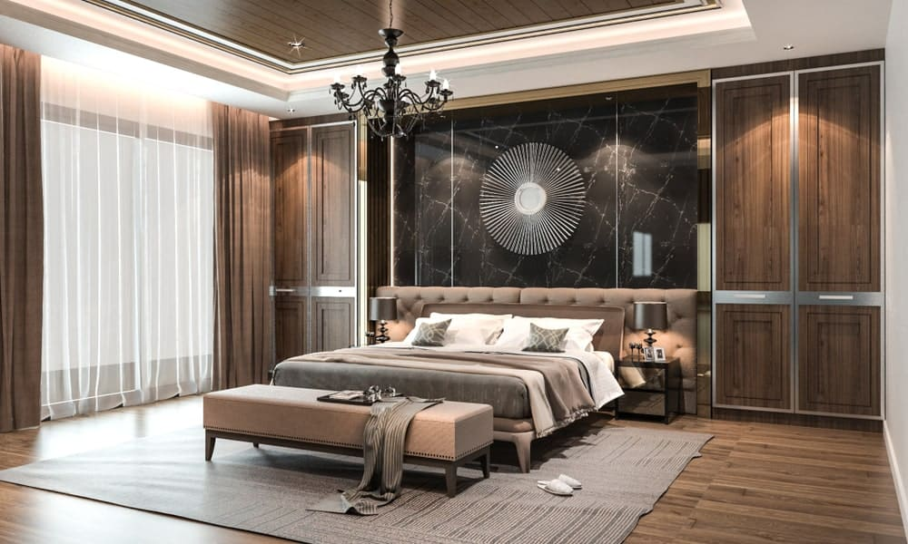 Classy primary bedroom boasts a wrought iron chandelier and sunburst decor mounted on the black marble wall. It has a cozy bed with custom tufted headboards placed in between built-in cabinets.