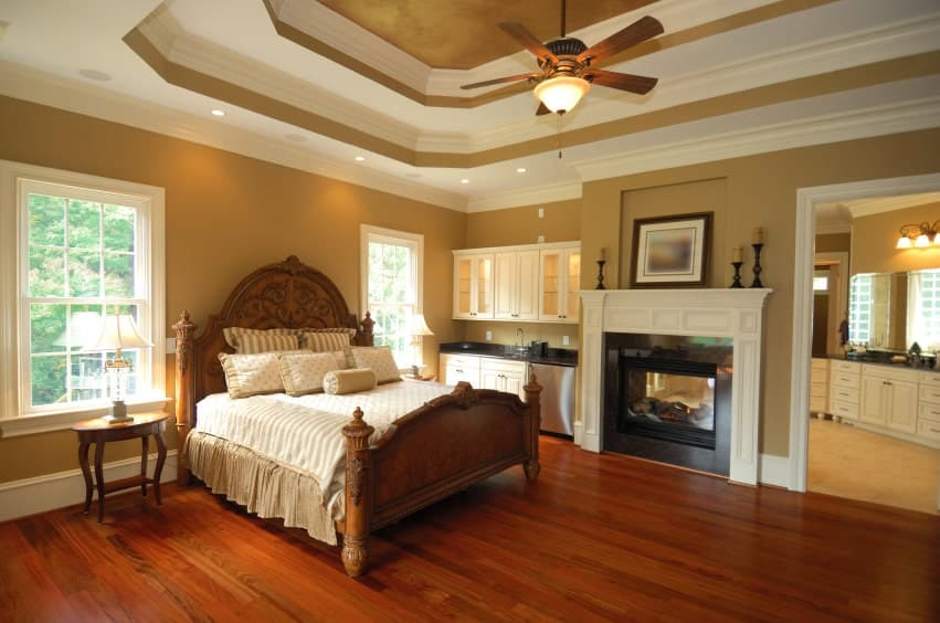 Classic brown primary bedroom offers a fireplace and carved wood bed illuminated by flush and recessed lights mounted on the double tray ceiling.