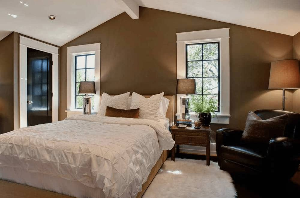 Natural wood nightstands and mirrored table lamps flank a cozy bed in this brown primary bedroom boasting a white shaggy rug and black leather armchair lighted by a traditional floor lamp.