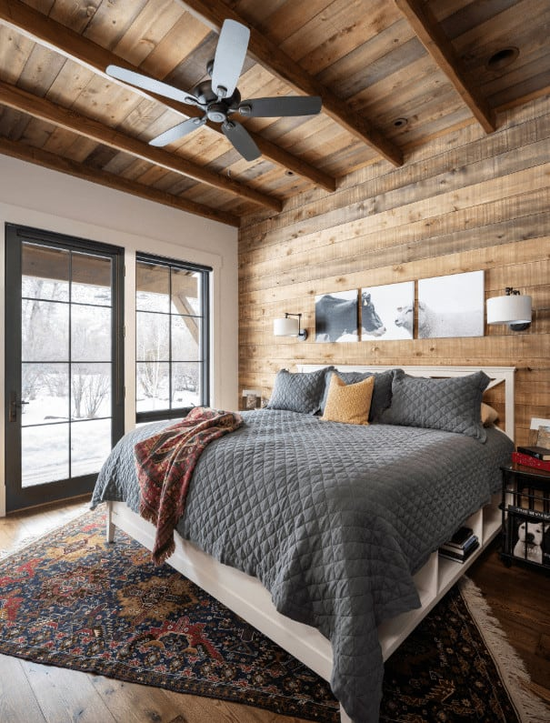 Cozy primary bedroom with multi-panel wall art and white bed on a tasseled rug wrapped in a gray quilt. It has black framed windows and wood plank ceiling mounted with a fan.