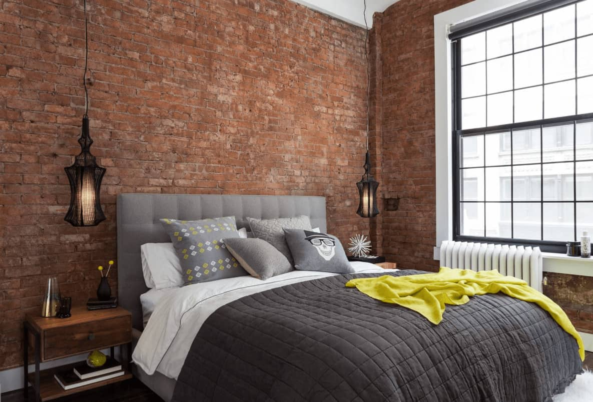 A pair of stylish black pendants hang over the wooden nightstands with a gray tufted bed in the middle placed against the brown brick walls.