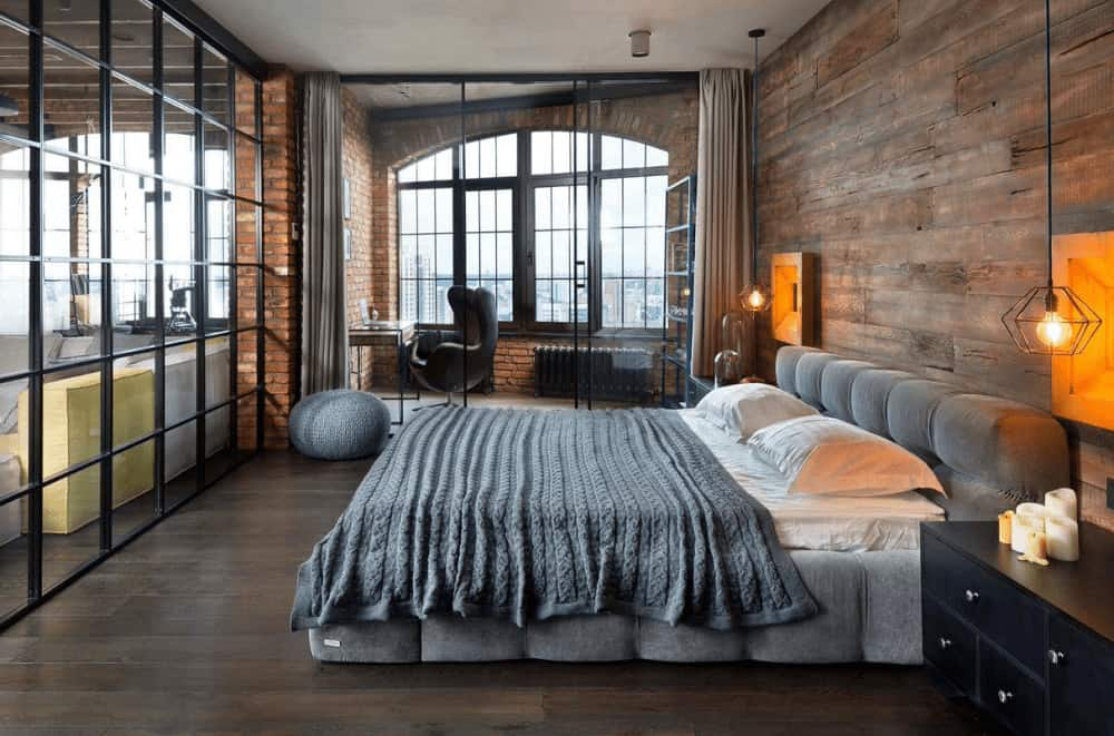 Industrial primary bedroom illuminated by geometric pendant lights that hung over the black nightstands flanking a gray tufted bed. It has wide plank flooring and a glazed door that leads to the office area.