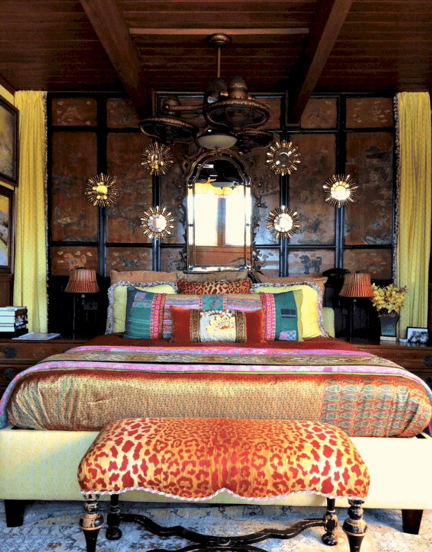 An animal printed bench sits in front of the yellow patterned bed decorated with sunburst and ornate arched mirrors. It is lighted by a unique chandelier that hung from the wood beam ceiling.