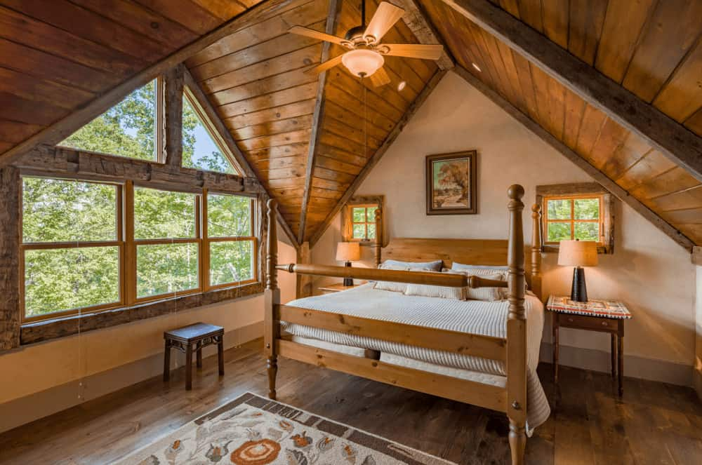 A framed wall art hangs above the wooden bed in this rustic bedroom with glass paneled windows and vaulted ceiling clad in natural wood planks.