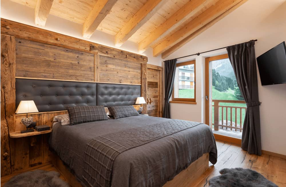 This primary bedroom showcases a wall mount TV and a wooden bed with custom tufted headboards fitted on the wood paneled wall. It includes gray drapes and shaggy rugs that lay on the hardwood flooring.