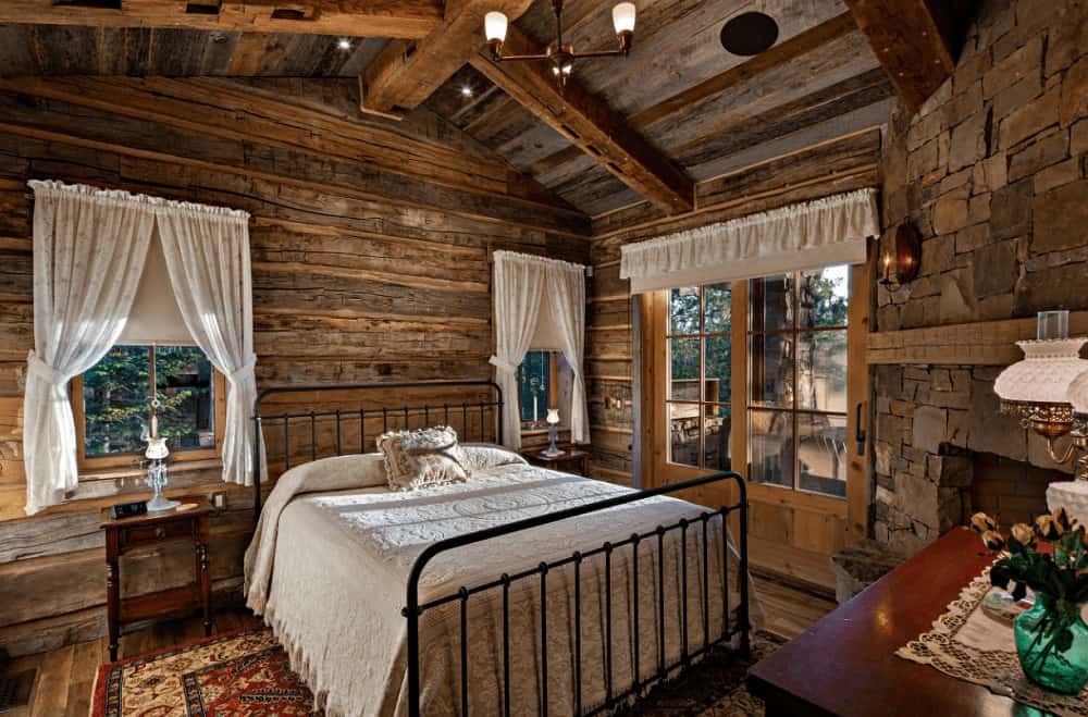 Rustic bedroom with a black metal bed and wooden nightstand topped with a green translucent flower vase. It is illuminated by recessed lights and a brass chandelier that hung from the vaulted ceiling.