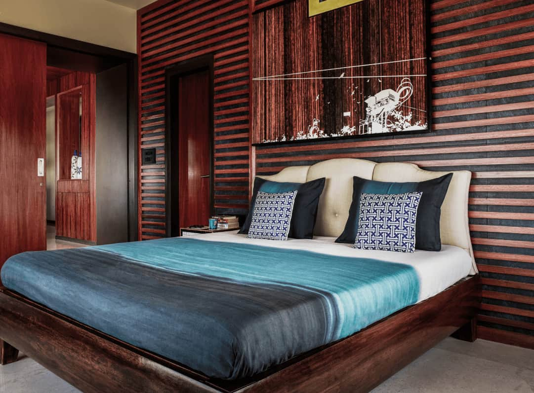 This primary bedroom showcases a lovely artwork that blends in with the wood paneled wall along with a wooden bed fitted with a beige tufted headboard.