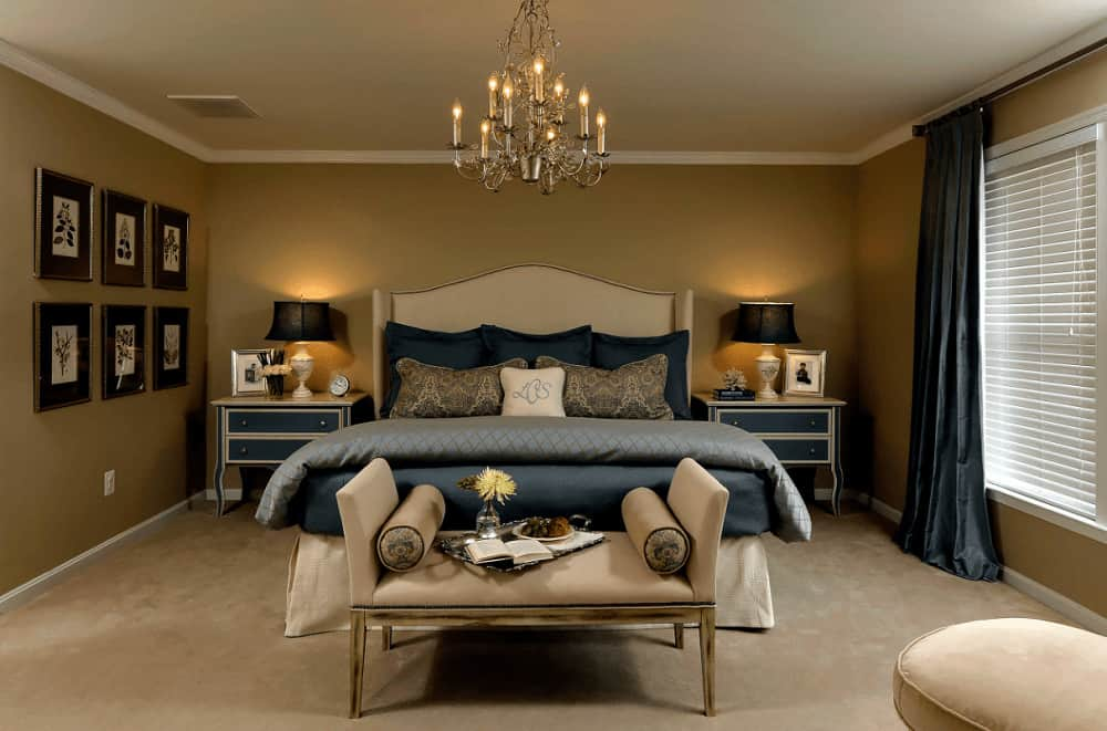 Classic brown primary bedroom decorated with gallery frames and a fancy chandelier that hung over the wingback bed flanked by blue nightstands and traditional table lamps.