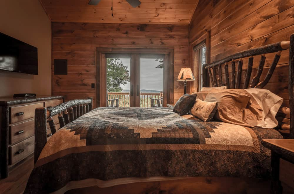 A log branch bed complements the drawer chest in this warm primary bedroom with a flat screen TV and table lamps that sit on wooden nightstands.
