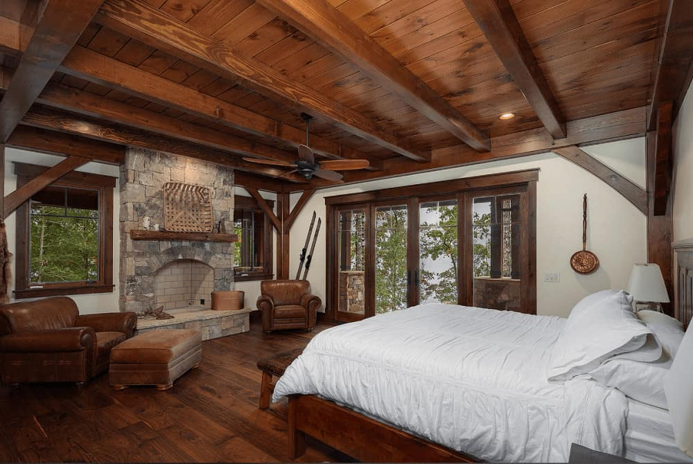 A wooden bed dressed in white bedding faces the stone brick fireplace topped with a rustic mantel and wicker wall art. It is flanked by brown leather armchairs over wide plank flooring.