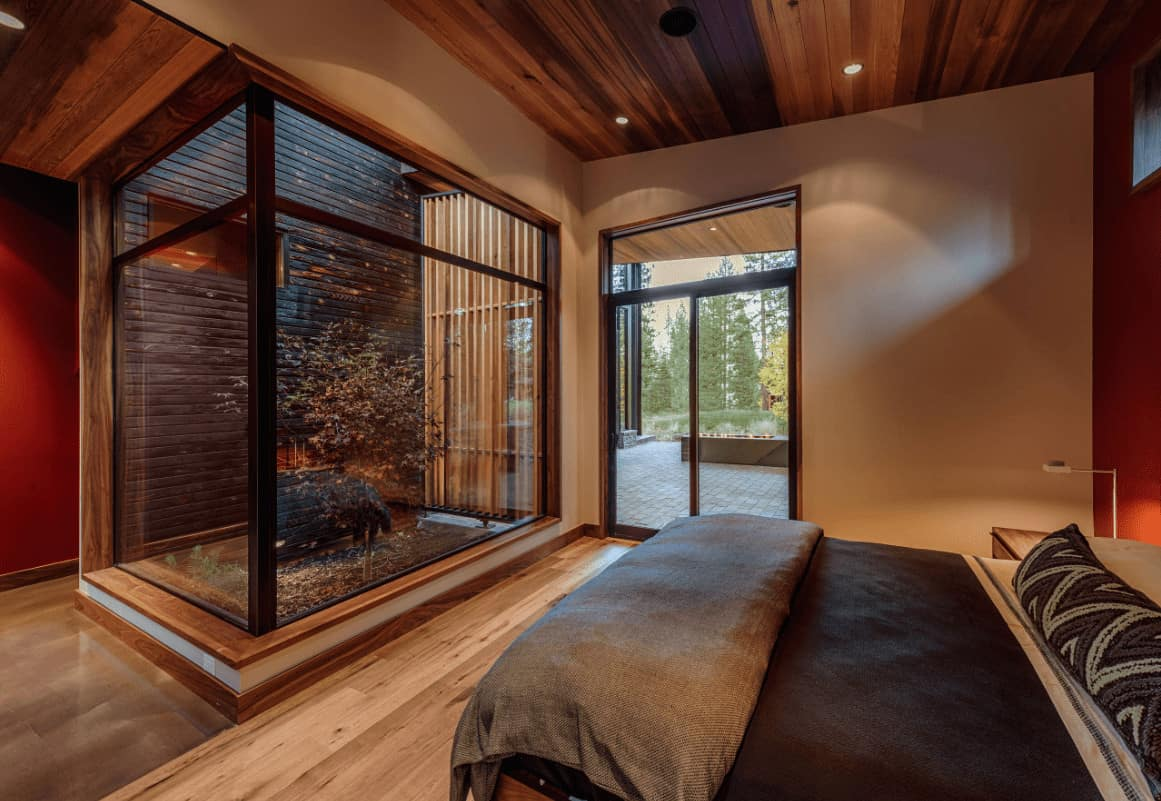 The sleek primary bedroom offers a comfy bed and a lovely plant enclosed in aluminum framed glass. It has light hardwood flooring and wood plank ceiling mounted with recessed lights.
