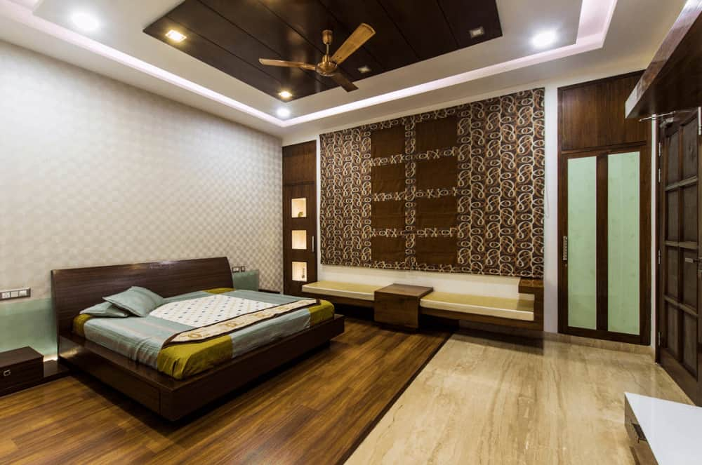 This primary bedroom offers a platform bed and a sleek seat on the side accented by a large patterned tapestry. It has hardwood flooring and tray ceiling mounted with a bronze fan.
