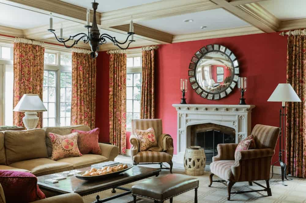 A candle chandelier that hung from the coffered ceiling illuminates this living room boasting comfy seats and a fireplace with candle holders and a concave mirror on top.