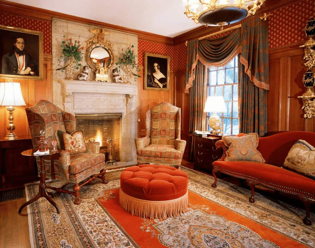Elegant living room clad in red patterned wallpaper and wooden wainscoting mounted with lovely portraits. It has a fireplace and classy seats over a bordered area rug.
