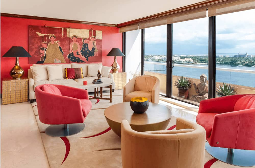 A multi-panel painting hangs over the beige sofa accompanied by cube end tables and sleek chairs surrounding a wooden coffee table. It has carpet flooring and full height glazing overlooking a spectacular lake view.