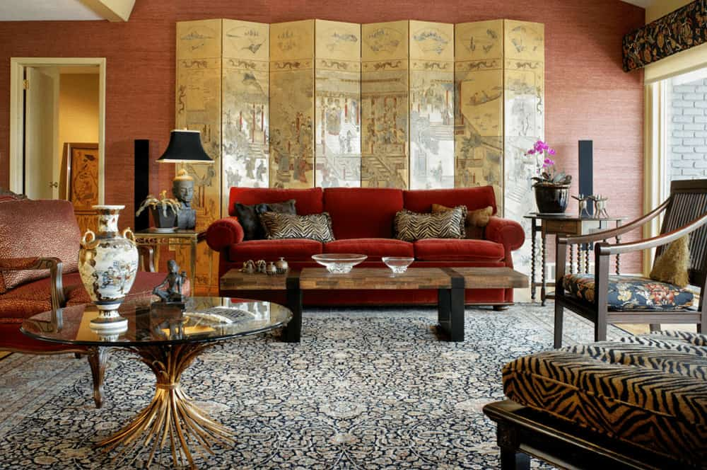 Classic living room with cozy seats and various tables that sit on a floral area rug. It includes a painted screen that sets a classy backdrop to the red sectional sofa.