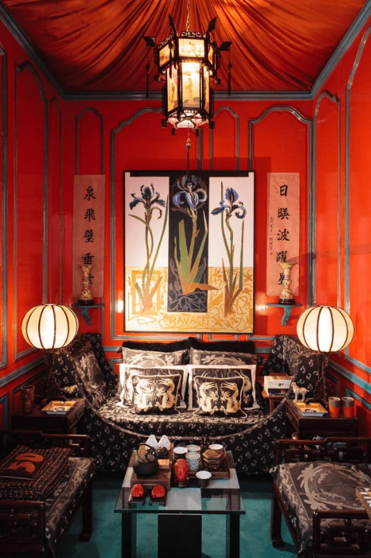 Small living room with classy sits and gorgeous artwork mounted on the red wainscoted walls. It is illuminated by round table lamps and a lantern pendant light that hung from the canopy ceiling.