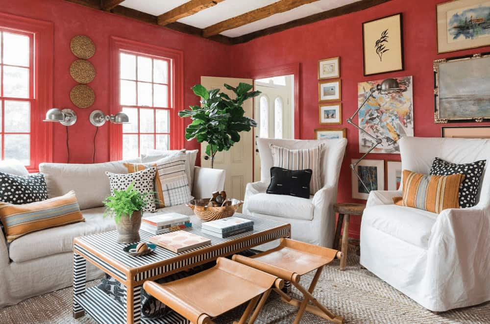 Fresh living room offers a fiddle leaf fig plant and white skirted seats paired with a striped coffee table. It has a gallery wall and a regular ceiling lined with rustic wood beams.