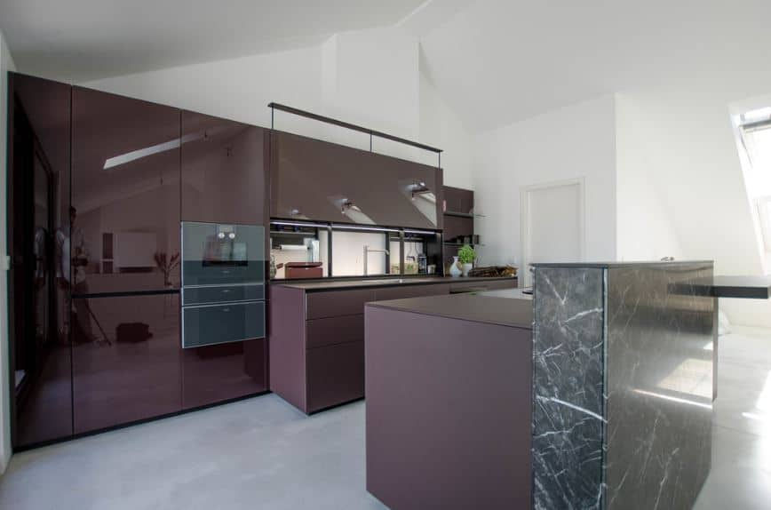 The white cathedral ceiling and gray concrete flooring are both contrasted by the large dark purple structures of the peninsula and kitchen island that has a raised breakfast bar attached to it made of green marble that goes well with the modern cabinets and drawers.