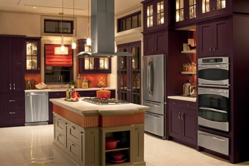 The earthy hue of the wooden kitchen island in the middle of the beige flooring is a nice nice contrast for the surrounding cabinetry that dominates the walls of this kitchen. These cabinetry have a purple hue paired with various stainless steel appliances and a bold orange backsplash.