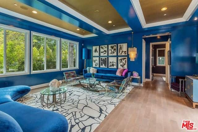 This living room is designed with a photo gallery mounted above the blue velvet sofa that's lighted by a cascading chandelier. It is accompanied by modern seats and glass top coffee tables on a brown area rug over the wide plank flooring.