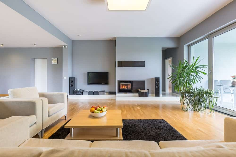Spacious living room with brown velvet seats and a wooden coffee table that blends in with the hardwood flooring. It includes a wall mount TV and a fireplace fitted on the light blue wall.