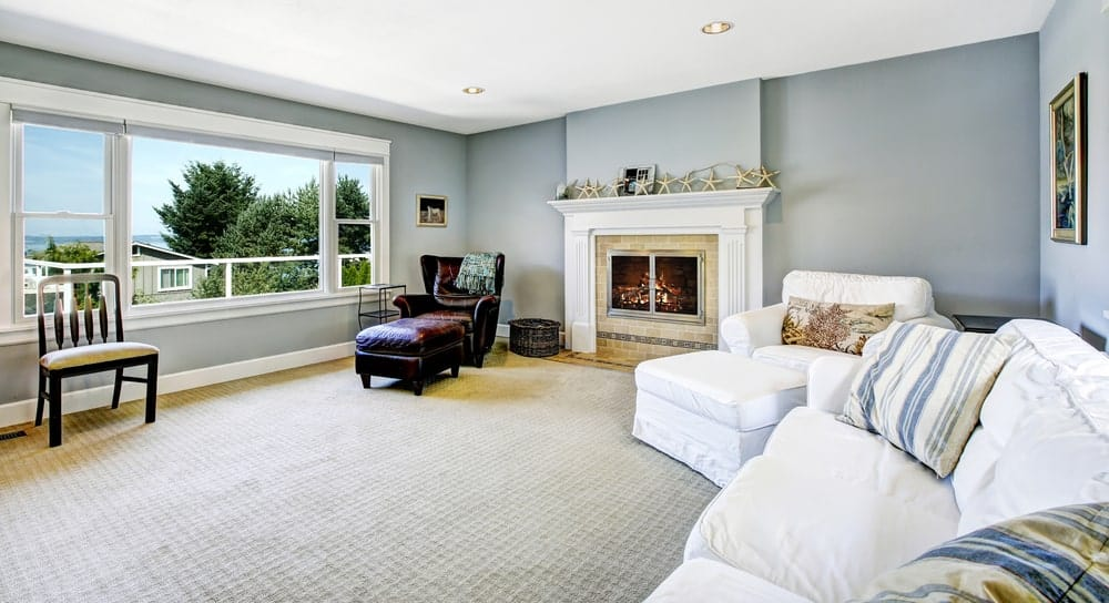 This living room offers white seats and a fireplace along with a leather wingback lounge chair by the glazed windows allowing natural light in.