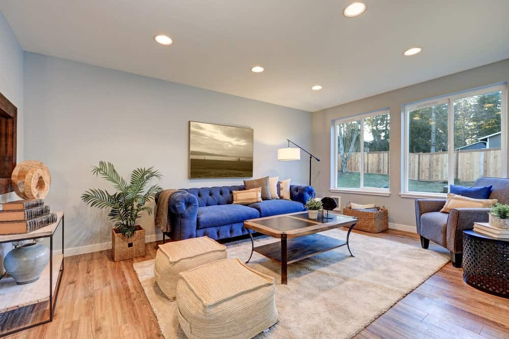 A blue tufted sofa stands out in this living room with natural hardwood flooring and glazed windows overlooking the lush lawn that's enclosed in a wooden fence.