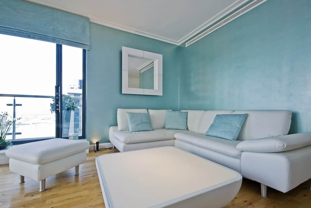 The sleek living room features a white coffee table and cushioned ottoman that complements the sofa accented with sky blue pillows. It has hardwood flooring and blue walls mounted with a white framed mirror.