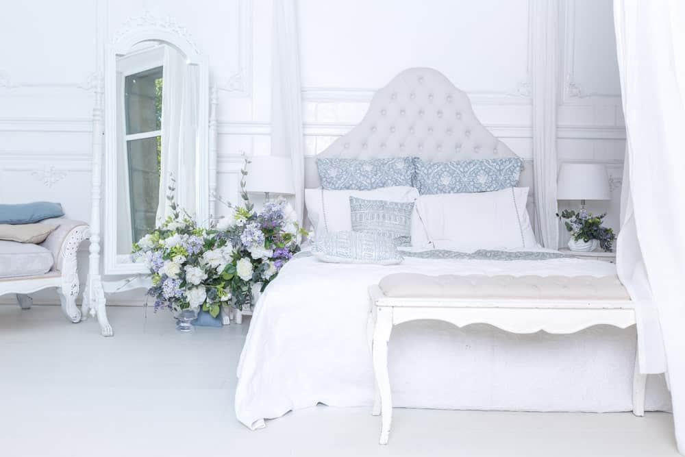Large primary bedroom featuring a gorgeous bed setup with beautiful flowers on its side lighted by table lamps and is surrounded by white walls and floors.