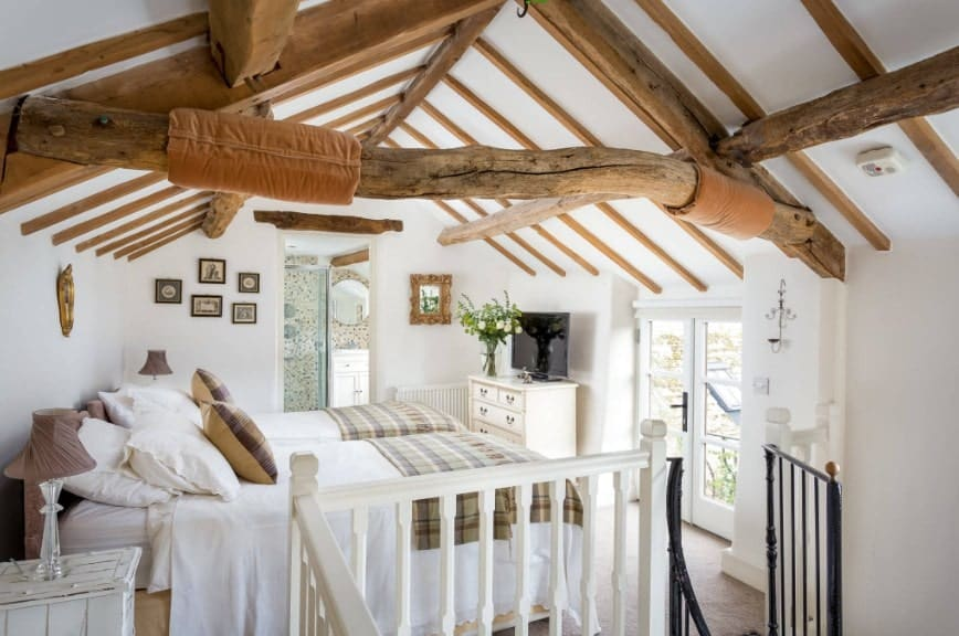 Large primary bedroom featuring white walls and a ceiling with exposed beams. The room boasts two beds with a TV on top of the cabinet.