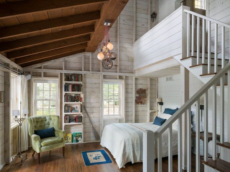 This primary bedroom boasts a wooden ceiling and wooden walls, along with hardwood flooring. It has a staircase leading to the bathroom.