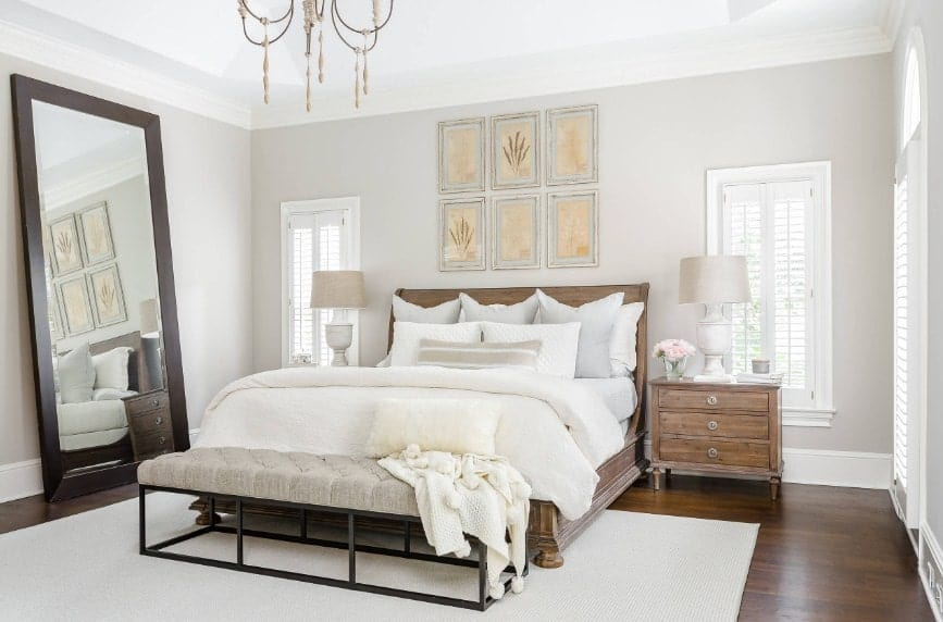 Spacious primary bedroom featuring a large bed with rustic bedside tables topped by classy table lamps. The room features hardwood flooring topped by a white area rug.