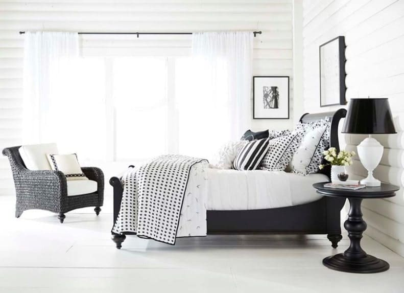 Bright primary bedroom with a black accent. It has white flooring and white walls, along with a black bed frame and other furniture finished in black.