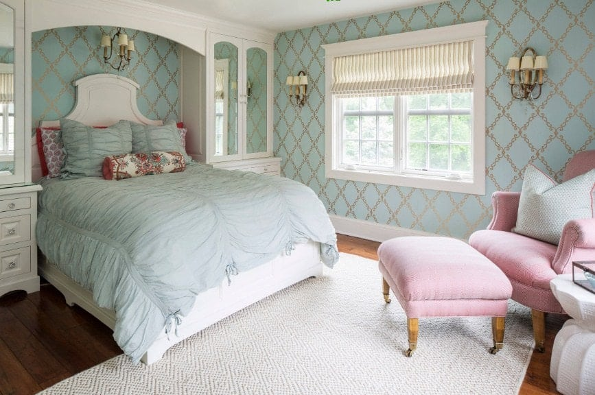 Primary bedroom with elegant green walls lighted by wall lights. The room offers a large classy bed along with a pink chair with a footrest on the side. The hardwood flooring is topped by a white area rug.