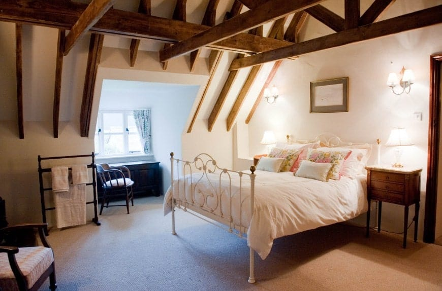 Large primary bedroom featuring carpet flooring and a ceiling with exposed beams. The room offers a nice white bed lighted by wall lights.