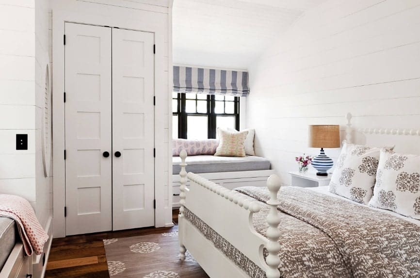 Primary bedroom featuring hardwood flooring, white walls and a white ceiling. The room offers a large classy bed along with a bench seating by the windows.