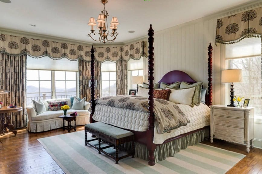 Large primary bedroom with elegant window curtains and a gorgeous chandelier. The room has a large cozy bed and a nice couch near the windows.