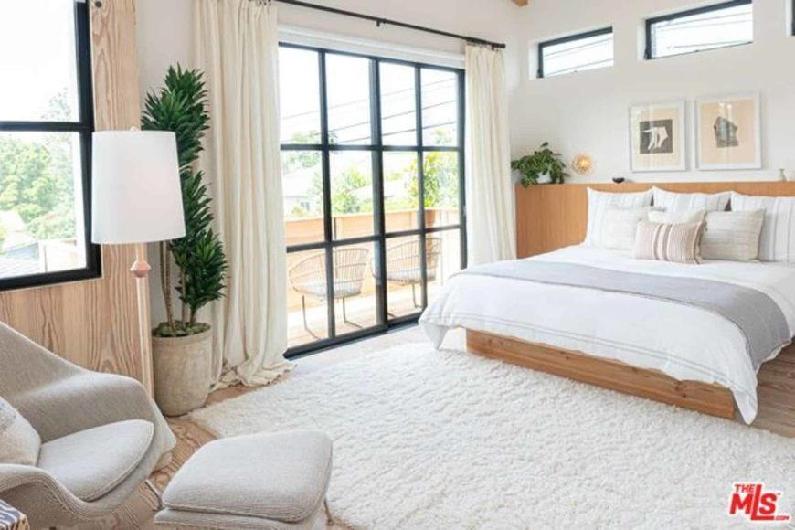 This is an airy and bright Scandinavian-style bedroom with its white ceiling and walls matched with the brightness from the French sliding glass doors leading to a balcony. The traditional wooden bed melds with the hardwood flooring that is covered by a white area rug.