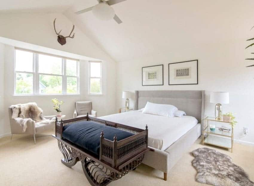 This Scandinavian-Style primary bedroom boasts classy carpet flooring and a luxurious bed under the white vaulted ceiling.