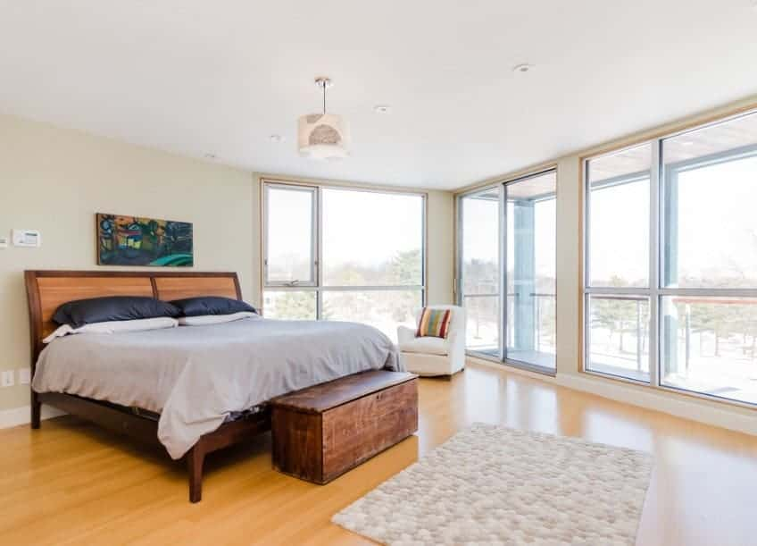 This Scandinavian-Style primary bedroom features glass windows and hardwood floors. There's a private balcony as well, overlooking the great outdoor views.