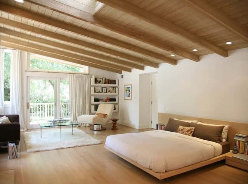 Large Scandinavian-Style primary bedroom featuring a glamorous wooden ceiling with beams matching the hardwood flooring. The bed looks very stylish and romantic. There's a reading nook on the side as well.