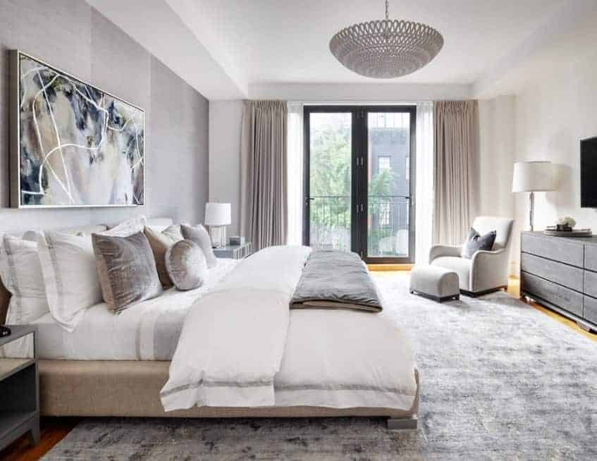 Stylish Scandinavian-Style primary bedroom featuring a massive gray rug. The wall decor adds charm to the area.