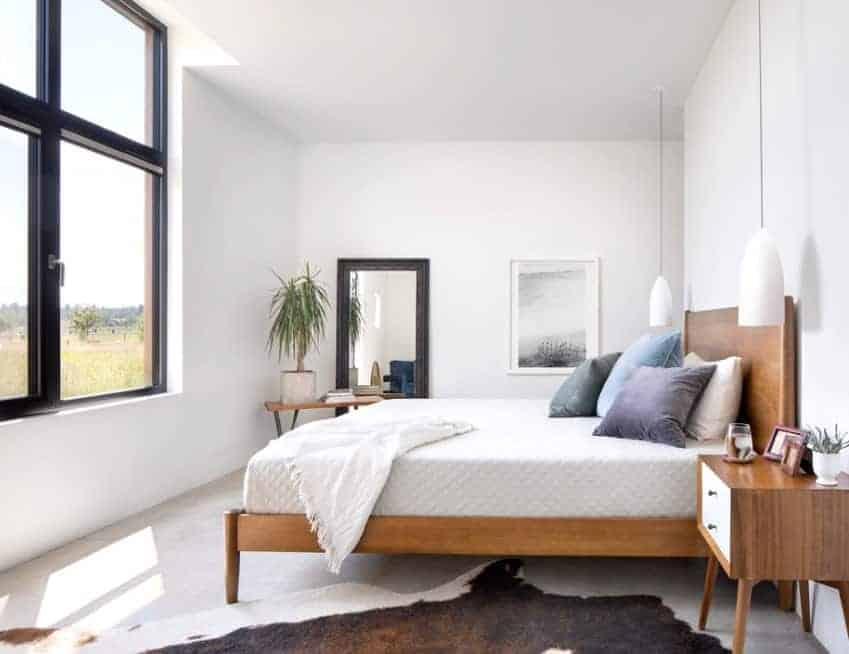 A classy Scandinavian-Style primary bedroom featuring white walls and modish pendant lights. The rug covering the white flooring looks very stylish.