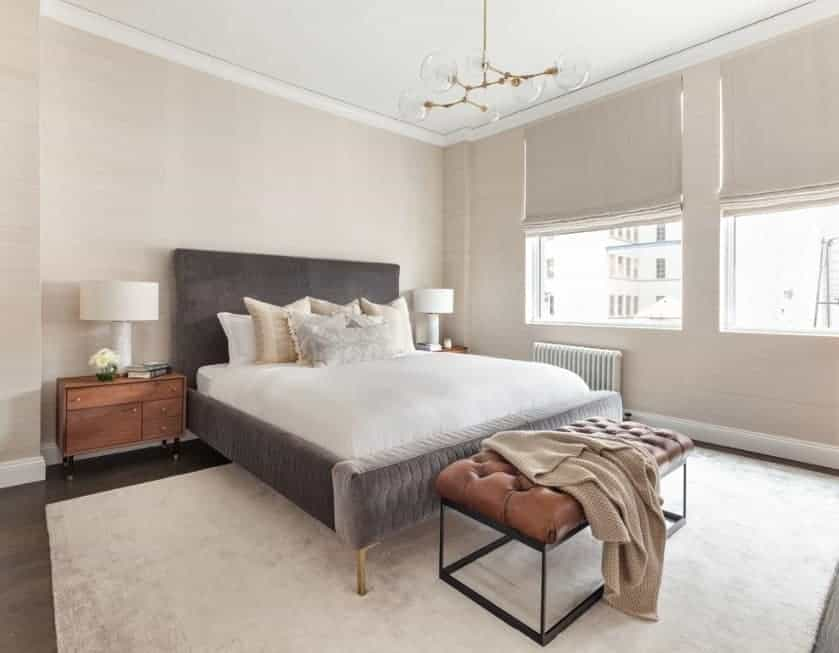 A modish Scandinavian-Style primary bedroom with a luxurious bed and a classy rug covering the hardwood flooring. The room is surrounded by charming beige walls.